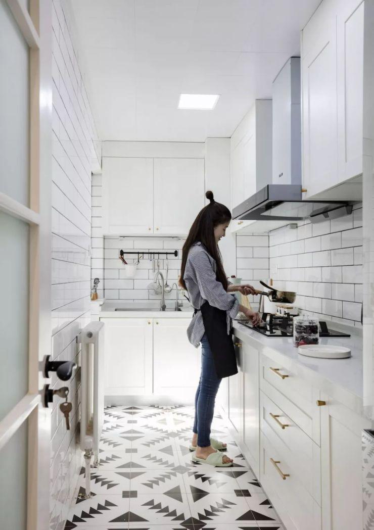 厨房地面拼贴黑白花砖,墙面采用白色瓷砖工字铺贴,白色橱柜金色拉手